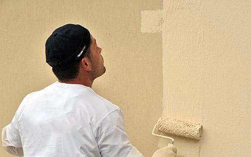 Homme qui applique la peinture sur mur extérieur