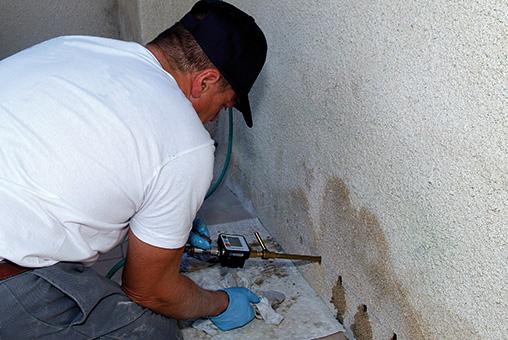 Homme qui applique traitement contre mur humide
